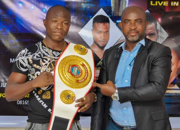 Scribe of Nigeria Boxing Board Control Remi Aboderin (Right) with a boxer. Credit : Akeem Busari